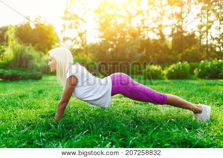 Picture of sports woman engaged in fitness on lawn in park on summer day. Lensflare effect