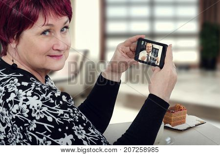 One aged woman holds mobile phone with virtual doctor attentively reviewing her brain x-ray results. Patient contacts expert via cellphone with telemedicine application