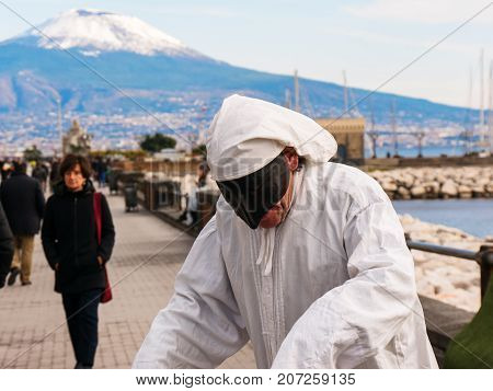 Naples 2017 January Italy: Pulcinella and people, traditional Neapolitan mask gestures with snowy Vesuvius in the background in the Gulf of Naples. Actor recites the part of Pulcinella in the street, among the people who pass, on the promenade of Naples