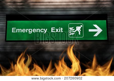 Emergency exit sign green color with light and arrow pointing to exit gate with while fire. safety concept