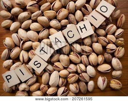 A pile of pistachio nuts with the word