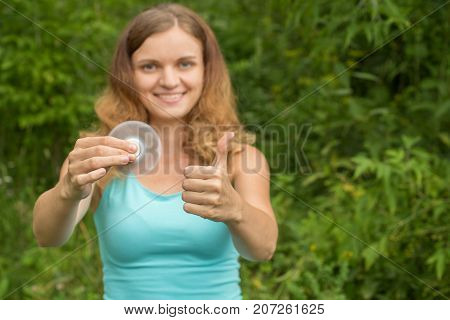 Young beautiful brunette girl smiles and fools around with moving spinners in hands in summer