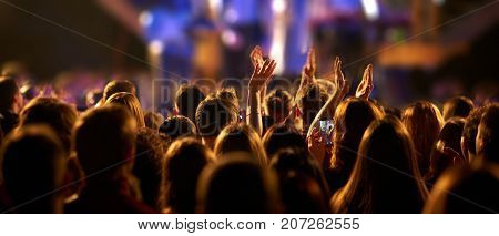 Audience with hands raised at a music festival and lights streaming down from above the stage. Selective focus.