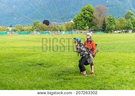 Interlaken Switzerland - May 26 2016: Tandem paraglider on the green lawn after landing in Interlaken Switzerland.