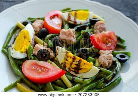 Summer warm salad with cooked green beans tuna tomatoes boiled eggs and sauce balsamico glassa in white plate on black stone background. Healthy eating concept.