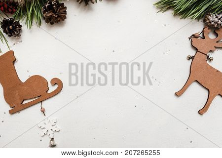 Festive background of winter holidays decoration. Pine branch with strobila and wooden ornaments on white backdrop, top view copy space. Celebration, New Year, Christmas, homemade decor concept