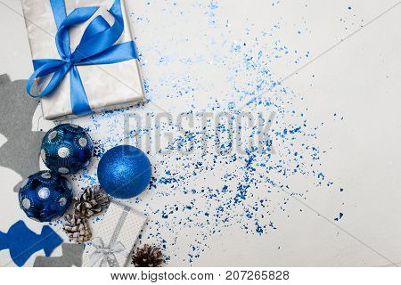 Background of Christmas decor and gifts top view. Wrapped in silver paper present, ornament blue balls and felt fir tree with spangles spread around, copy space on right. Handmade decoration concept