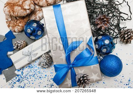 Background of Christmas decor and gifts. Close up of presents, ornament blue balls, sweet cakes and felt fir tree with spangles spread around. Festive backdrop of handmade decoration concept