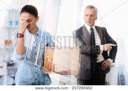 Get out. Depressed young woman crying and holding a box with her belonging while her boss unemploying her