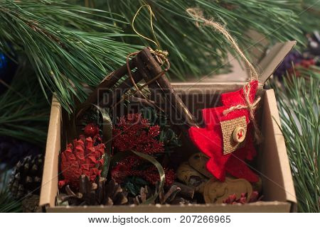 Festive box with decoration. Colorful strobilas, felt fir tree with sweet cookies and handmade wooden frame gathering in carton, close up picture. New Year and Christmas traditions and decor concept