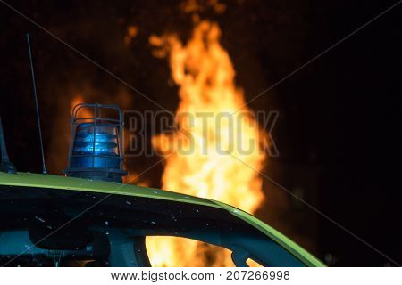 Detail Of Flashing Blue Siren Light On Roof Of Emergency Vehicle And Fire In Background
