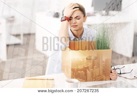 How to live on. Depressed young woman being in despair and sitting in the office with her belongings after dismissal