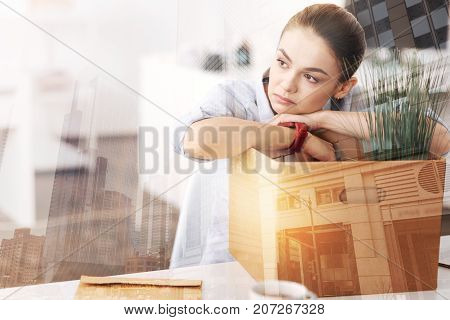 Think about future. Young unemployed woman sitting in the office with the box of her belongings after being fired