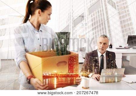 Time to say good bye. Depressed unemployed young woman holding the box with her belongings and looking at her boss who is sitting in the background
