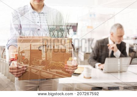 Flow of personnel. Close up of an unemployed woman holding the box with her belongings while her boss sitting in the background