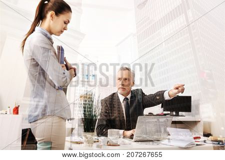 Get out. Furious professianal boss sitting at the table and dismissing a young unprofessional woman