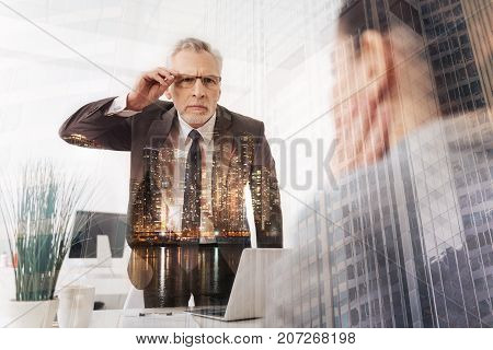 What did you say. Concentrated strict boss holding his glasses and looking at his female employee while standing in the office