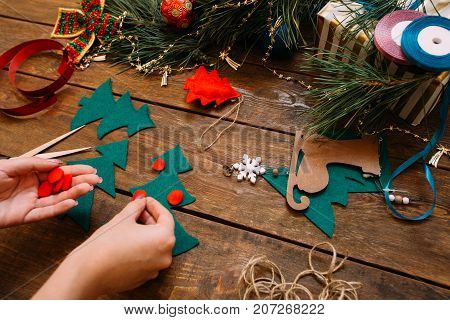 Holiday preparation. Christmas and New Year. Unrecognizable woman decorating green felt fir tree on wooden background, festive handmade decoration concept. View from shoulder