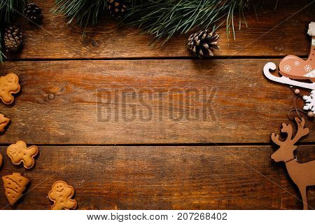 Christmas and New Year holiday background. Close up handmade ornaments of skate and deer, gingerbread cookiest and pine with strobila on wooden table, festive decoration concept with free space