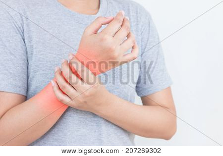 Young woman has pain in wrist on white background.