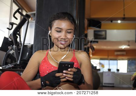 young beautiful and attractive Asian sport woman at fitness center during training workout pause using mobile phone texting and messaging happy in internet social media and network concept