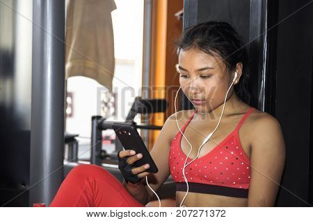 young beautiful and attractive Asian sport woman at fitness center during training workout pause using mobile phone texting and messaging in internet social media and network concept