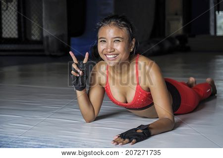 young happy and beautiful sweaty Asian woman in sport clothes stretching on gym dojo floor smiling posing corporate in hard training workout and healthy sporty lifestyle concept giving victory sign