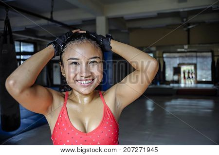 corporate portrait of happy beautiful and sweaty young Asian woman in sport training cloths smiling relaxed at gym dojo after workout exercise in fitness and healthy lifestyle concept