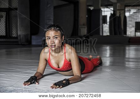 young beautiful sweaty Asian woman in sport clothes stretching on gym dojo floor smiling posing corporate in hard training workout and healthy sporty lifestyle concept