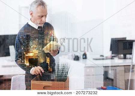 Last things to do. Waist up of unemployed adult man holding his notebook and packing the belongings while standing in the office