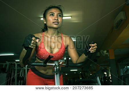 young beautiful and sweaty Asian active woman training hard cycling and riding on static bike workout at gym in sport fitness body care and healthy lifestyle concept and bicycle fitness gear
