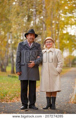 Portrait of happy senior couple embracing at park during autumn