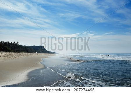 The ocean beach is in the horizon with small waves and haze.
