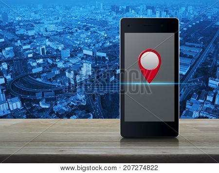 Map pin location button on modern smart phone screen on wooden table over city tower street and expressway Map pointer navigation concept