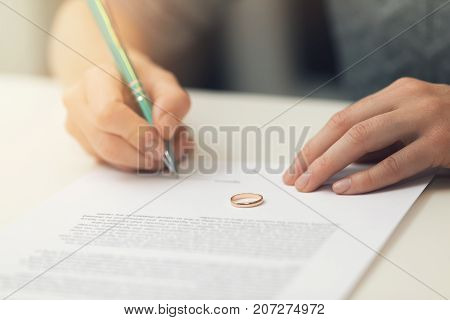 woman signing marriage divorce papers. family conflict