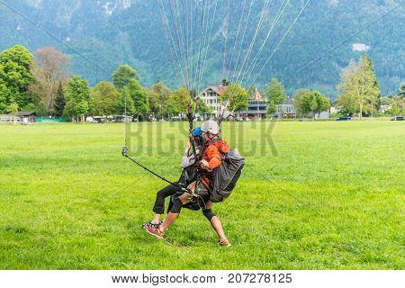 Interlaken Switzerland - May 26 2016: Tandem paragliding landing after flight over the Swiss Alps in Interlaken Switzerland.