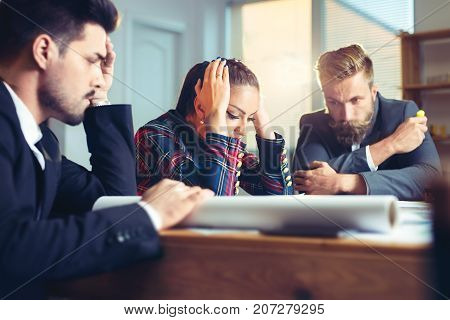 Frustrated business people sitting at the table in office, arguing while discussing project.