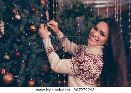 Feast is coming! Charming lady with long hairstyle is excited setting the decorative pinetree in knitted cute traditional x mas costume with ornament enjoy garland of sparkles on window