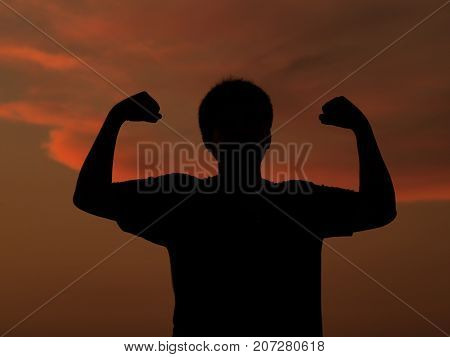 Silhouette successful winner young man gesturing raising arms at sunset against orange sky background. Positive human emotion facial expression. Life perception and achievement.