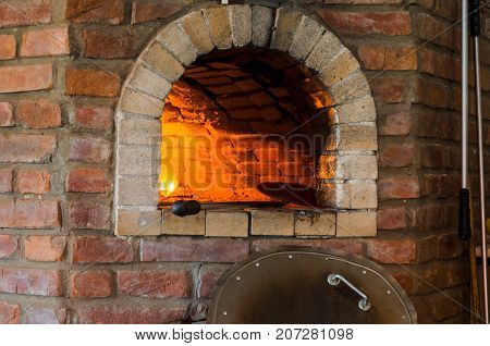 Fire in stone oven. Oven made of brick and clay on the wood. Oven for pizza. Brick oven.