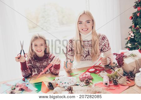 Small Lovely Cheerful Blonde With Her Mom Are Doing Handcraft Activity. Desktop Full Of Tapes, Pine-