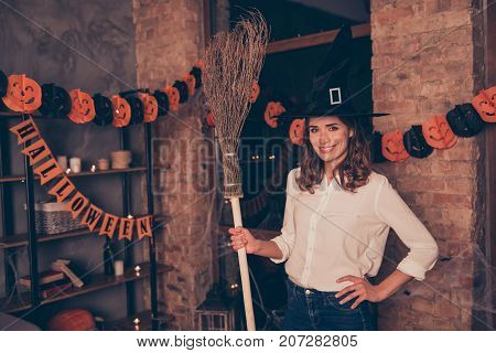Gorgeous charming attractive enchantress in elegant clothing long worlock headwear smart formal wear and jeans having a broom stick in her arm in evening indoors in a loft style room