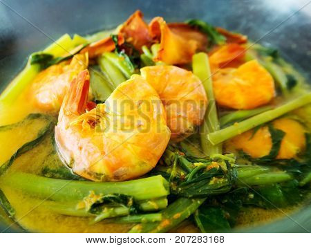 Yellow curry shrimp prawn with morning glory. Traditional local southern food. Delicious sour and spicy soup.