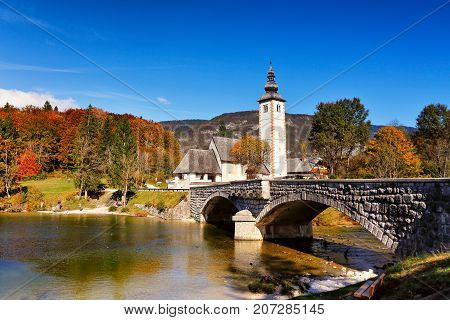 Colorful Autumn Day In Ancient Village With Old Bridge And Church