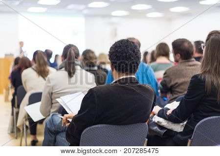 Business and entrepreneurship symposium. Female speaker giving a talk at business meeting. Audience in conference hall. Rear view of unrecognized participants making notes in audience.
