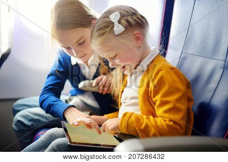 Adorable Little Girls Traveling By An Airplane. Children Sitting By Aircraft Window And Using A Digi