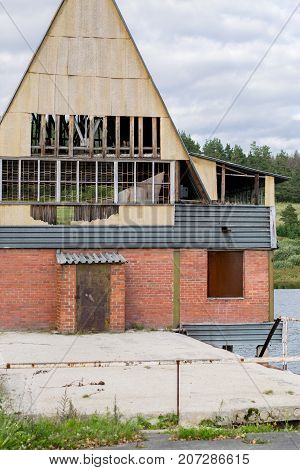 Destroyed house on a river, Redbricks building with broken windows Russia, the Urals
