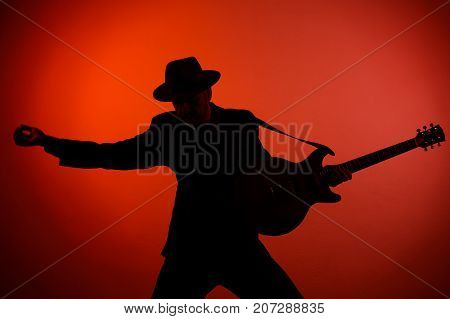 silhouette of a guitarist in a hat on a red background.
