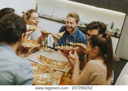 Group Of Young People Eating Pizza And Drinking Cider