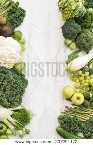 Green and white vegetables and fruits on the white wooden table, copy space for text in the middle, top view, vertical, selective focus